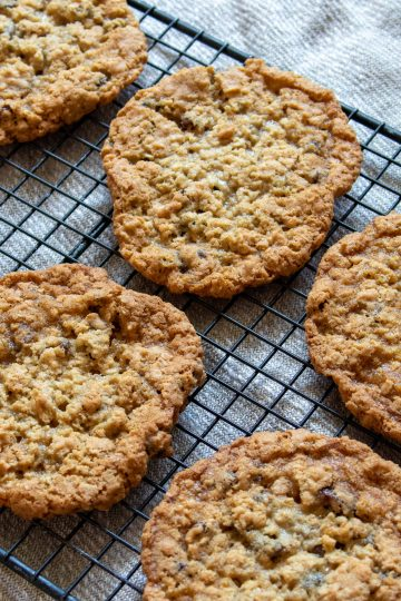 A batch of oatmeal raisin cookies cooling on a rack