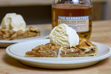 A slice of apple galette with a scoop of ice cream and a bottle of single malt scotch in the background