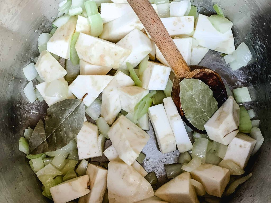 chopped celery root, onion, and bay leaves in a pot with a wooden spoon