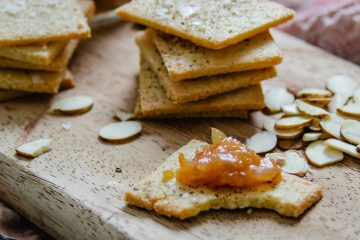 Almond Parmesan crackers with chutney on a wooden serving board
