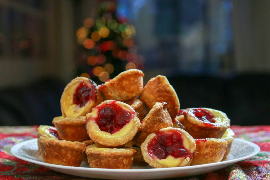 A plate full of cranberry yogurt custard tartlets with a lit up Christmas tree in the background