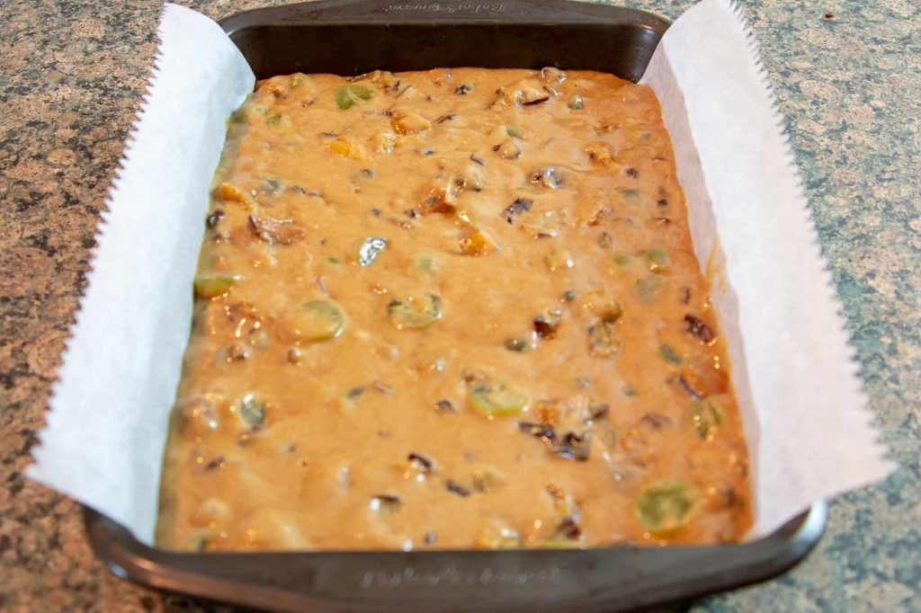 Fruit cake batter in a brownie tin ready for the oven