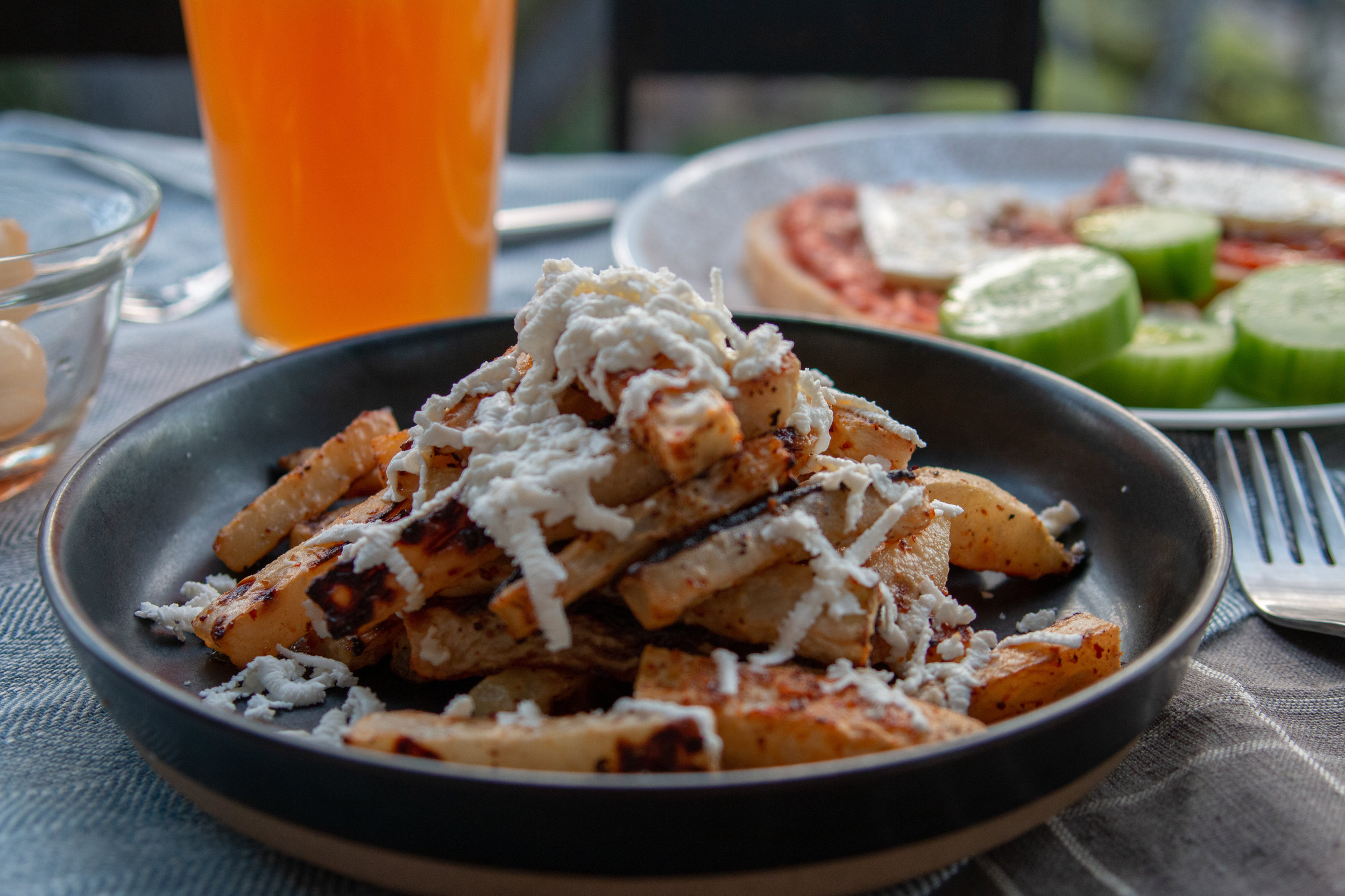 A big plate of kohlrabi fries with grated feta cheese