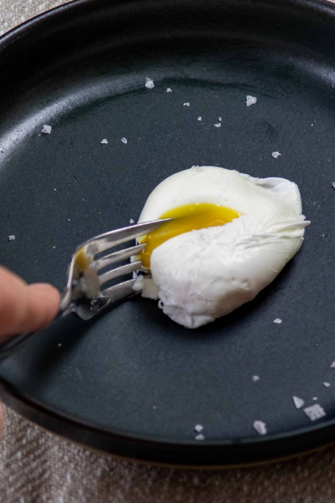 cutting into a soft poached egg on a plate