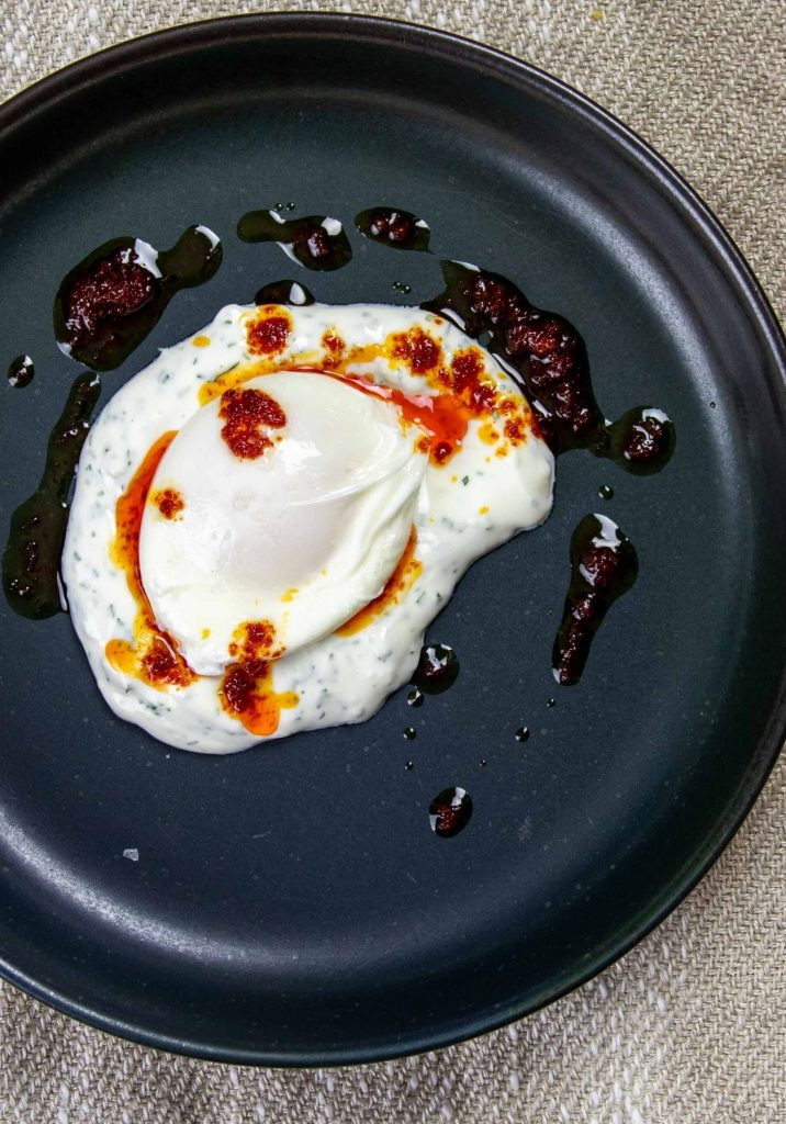 Poached eggs in savoury yogurt with chili oil