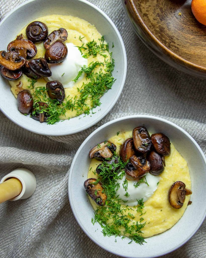two bowls of polenta topped with poached eggs, roasted mushrooms and fresh dill