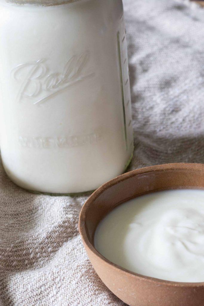 a small bowl and a jar of plain yogurt